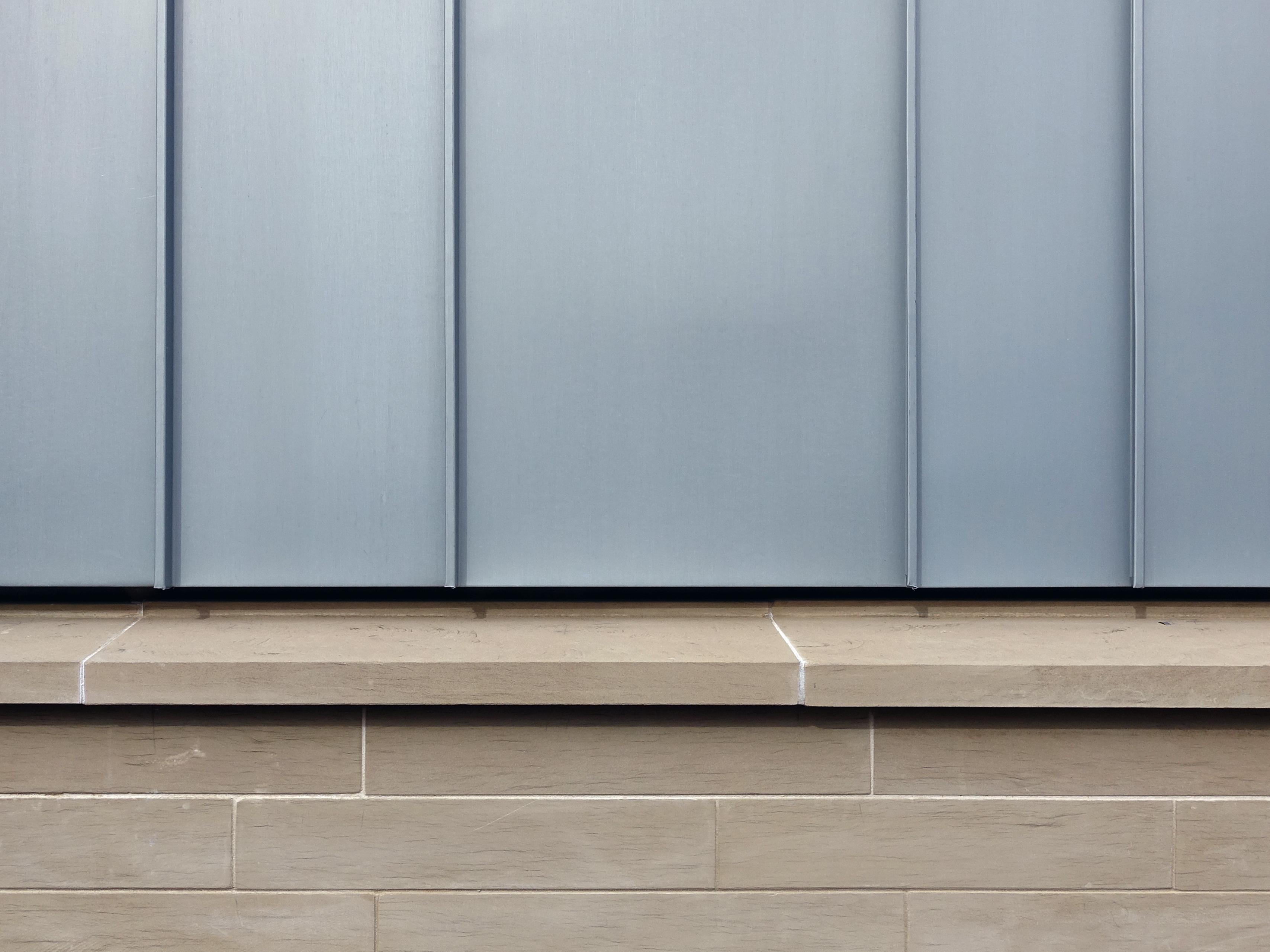 Gemeindehaus Dahenfeld, Detail Fassade - Stehfalz trifft Sandstein