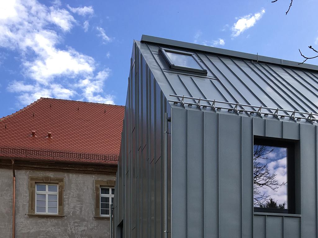 Gemeindehaus Dahenfeld, Biberschwanzziegel und Titanzinkfassade
